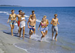Group of teenagers jogging on the beach stock photo