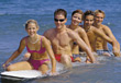 Group of teenagers paddling on a large surfboard in the ocean stock photo