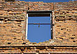Damaged Grunge Bricks Wall With Empty Window On The Blue Sky Background stock image