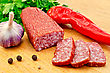 Mexican Food Half Stick Of Salami, Cut Three Pieces Of Sausage, Garlic, Red Pepper, Black Pepper And Parsley On A Wooden Board stock photo