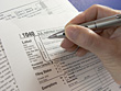 Hand Filling Out Tax Form 1040 stock photo