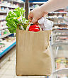 Hand Holding A Paper Bag With Groceries In A Supermarket stock image