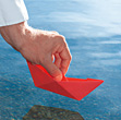 Hand Holding Red Origami Boat Over Water stock photography