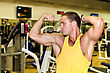 Handsome Bodybuilder Showing His Muscular Arms In Gym stock image
