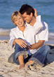 Happy Couple Sitting on Beach stock photo