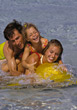 Happy family embracing in the waves at the beach stock photography