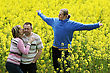 Happy Middle-aged Couple And Their Son In Flower Meadow