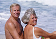 Happy Older Couple Sitting at Beach stock photo