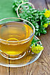 Healing Herbal Tea In Glass Cup With Flowers Rhodiola Rosea, Green Cloth On A Background Of Wooden Boards stock photography