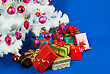 Heap Of The Christmas Presents Under Decorated White Evergreen Tree stock image