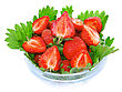 Close Heap Of Fresh Strawberries In Glass Bowl On Green Foliage . Isolated stock image