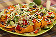 Heap Of Nachos With Vegetables On Green Plate stock photography