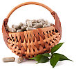 Herbal Drug Capsules In Wicker Basket Isolated On White Background Cutout. Alternative Medicine Concept