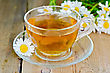 Herbal Tea In A Glass Cup, Fresh Chamomile Flowers On A Background Of Wooden Boards