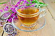 Herbal Tea In A Glass Cup, A Metal Strainer With Dry Flowers Fireweed, Fresh Flowers Of Fireweed On The Background Of Wooden Boards