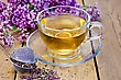 Herbal Tea In A Glass Cup, A Metal Strainer With Dry Flowers Marjoram, Fresh Flowers Of Oregano On The Background Of Wooden Boards