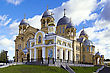 Holy Cross Cathedral, With Gray Zinc Dome And The Chapel Of St. Nicholas Monastery In The Background Of Blue Sky And White Clouds (Verhoturie City Of Sverdlovsk Region) stock photo