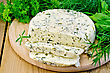 Homemade Round Cheese With Herbs And Spices Cut Into Slices On A Wooden Board stock photo
