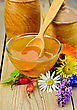 Honey In A Glass Bowl And Wooden Banks, Spoon, Berries Of Briar, Flowers On The Background Of Wooden Boards
