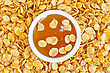 Honey In A White Cup On The Background Texture Of Golden Corn Flakes stock image