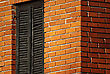 House Wall Made Of Bricks With Window Closed With Wooden Shades