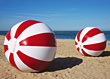 Huge Red & White Beach Balls In The Sand stock photography