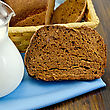 Hunk Of Homemade Rye Bread, Wicker Basket With Bread On A Blue Napkin On A Wooden Boards Background