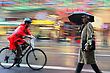 Intentional Motion Blur Abstract Of On Bike Delivery Moving Along With Traffic, Businessman Holding Umbrella Walking Motion Blur stock photo