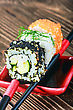 Rice Japanese Roll On Sticks On Wooden Table. Focus On The First Roll stock photography