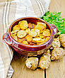 Jerusalem Artichokes Roasted In A Clay Pot, Parsley, Fresh Artichoke Tubers, Napkin On A Wooden Board stock photo