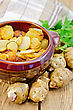 Jerusalem Artichokes Roasted In A Clay Pot, Parsley, Fresh Artichoke Tubers, Napkin Against A Wooden Board stock image