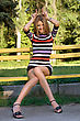 Joyful Young Blonde Sitting On A Park Bench