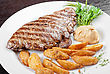 Juicy Beef Steak Stuffed With Beef Tongue And Cheese Served With Potatoes, Greenery And Sauce stock photo