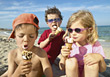 Kids Sitting in Sand Eating Icecream stock image