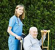 Kind Doctor Pushing Elderly Patient In Wheelchair stock photo