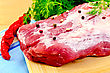 Large Piece Of Meat With Peas Of Different Peppers, Red Pepper, Parsley And Dill, Blue Cloth On The Background Of Wooden Boards stock photo