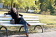 Laughing Young Woman Sitting On A Bench In Autumn Park