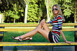 Leggy Young Blonde Sitting On A Park Bench