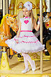 Magnificent Little Beautiful Girl In Pink And White Dress Standing On The Carousel stock photo