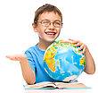 Playful Little Boy Is Holding Globe While Sitting At Table, Isolated Over White stock photo