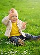 Little Boy Is Sitting On Green Meadow Covering His Eyes From The Sun