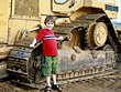 Little Boy Leaning on Bulldozer stock photography