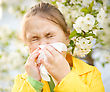 Little Girl Is Blowing Her Nose Near Spring Tree In Bloom stock photo