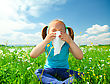 Little Girl Is Blowing Her Nose While Sitting On Green Meadow stock photo