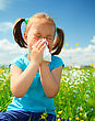Allergic Little Girl Is Blowing Her Nose While Sitting On Green Meadow stock photo