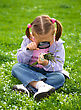 Playful Little Girl Is Sitting On Green Meadow Looking At Herbs Using Magnifier stock photo