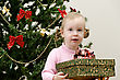 Little Girl Near The Christmas Tree Holding A Present stock image