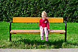 Smiling Little Girl Sitting On The Bench In The Park stock image