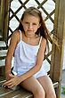 Little Girl Sitting On A Wooden Bench