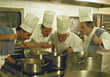 Male Chefs In Profesional Kitchen Looking At Pot stock photo